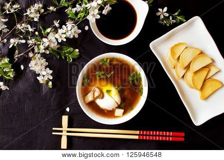 Asian miso soup with egg, tofu, mushrooms and seaweed, daikon slices and soy sauce on the black stone with flowering branches, top view