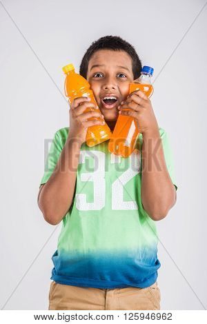 indian boy with cold drink bottle, asian boy holding cold drink bottle, small boy and cold drink, indian cute boy drinking mango juice or orange juice in plastic bottle