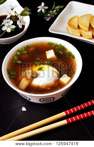 Asian miso soup with egg, tofu, mushrooms and seaweed, daikon slices and soy sauce on the black table with flowering branches