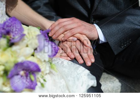 Man's and woman's hands together. Bride and groom holding hands. Blurred bouquet, focus on hand. Wedding rings.