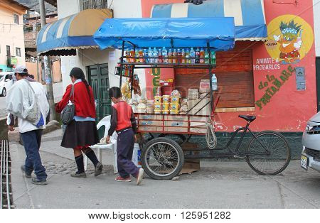 Cajamarca Peru - April 10 2016: A Peruvian family from the Sierras walks by a bicycle food cart selling bread cheese and drinks in Cajamarca Peru on April 10 2016