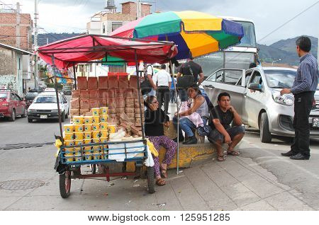 Cajamarca Peru - April 10 2016: People sit around a small food cart selling cookies cheese and other items at a bus stop in Cajamarca Peru on April 10 2016
