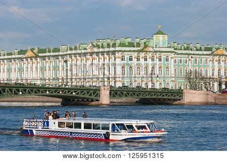 SAINT - PETERSBURG, RUSSIA - APRIL 16, 2016: Tourists in the excursion boat sail on The Neva River. On the background is The Palace Bridge and The State Hermitage Building (Winter Palace)