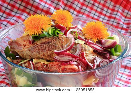 Pork with onions and dandelions in glass bowl