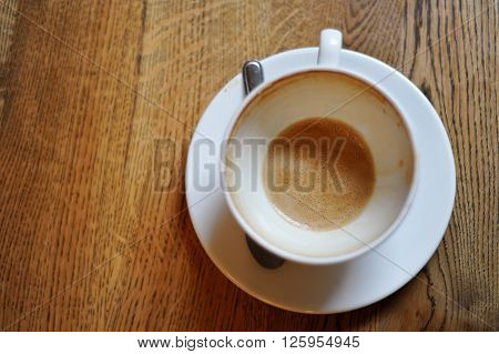 Cup with ended morning coffee latte on wooden table