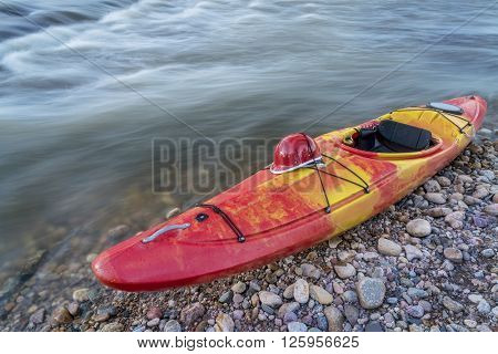 whitewater kayak with a helmet on deck on a river shore