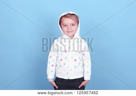 Cute kid girl 4-5 year old wearing hoodie with polka dots over blue. Looking at camera.