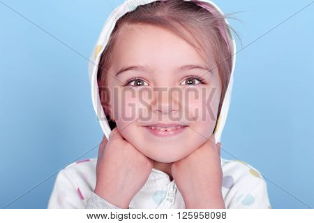 Smiling little girl wearing white hoodie with polka dots over blue. Posing in room. Looking at camera. Close up portrait.