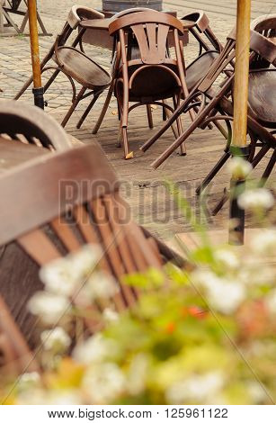 Piled chairs and table on restaurant terrace