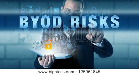 Managing director is touching BYOD RISKS on a virtual touch screen interface. Business phenomenon metaphor and information technology concept for Bring Your Own Device and IT consumerization.