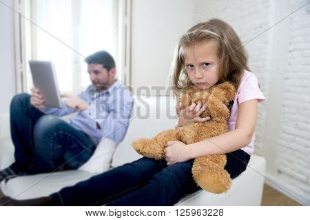 young internet addict father using digital tablet pad ignoring little sad daughter looking bored hugging teddy bear abandoned and disappointed with dad sitting on home couch sofa