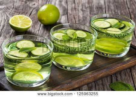 The Most Efficient Drink For Losing Belly Fat - Sassy Water: sliced cucumber lime and mint in the three glasses on a wooden tray on an old wooden table close-up