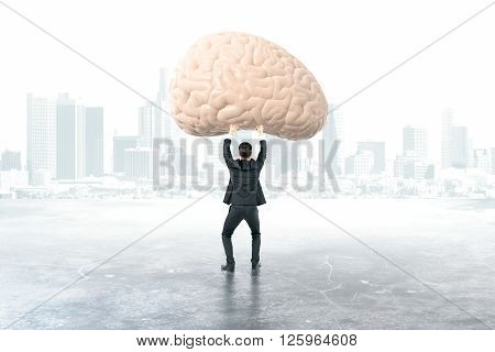 Businessman holding brain with foggy city in the background