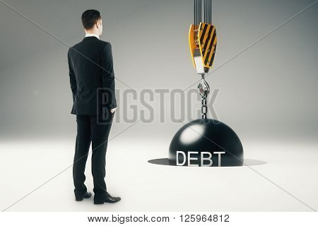 Debt concept with businessman looking at crane hook with wrecking ball going into pit. 3D Rendering