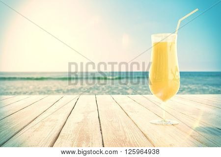 Yellow cocktail glass on wooden surface at the beach. 3D Rendering