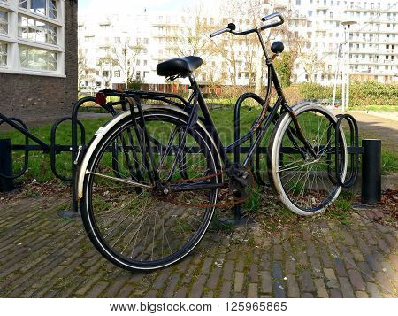 Typical old Dutch bike in bicycle rack or bicycle stand
