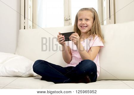 sweet cute and beautiful 6 or 7 years blond old female child in school uniform sitting on home sofa couch using internet app on mobile phone playing online game looking happy and relaxed