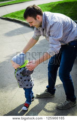 Father guiding his son with the first steps outside. Baby learning to walk holding father's hands. Toddler steps with the help of his father in spring park. Stylish boy in jeans and sneakers.