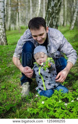 Father and son having fun in the spring park collecting flowers. Father's day. Toddler and father have fun outside.