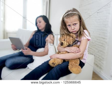 young internet addict mother using digital tablet pad ignoring little sad daughter looking bored hugging teddy bear abandoned and disappointed with her mum sitting on couch sofa
