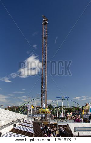 MUNICH, GERMANY - OCTOBER 02, 2015: Free fall tower at Oktoberfest with 80 meter height and the Alpinabahn rollercoaster in the background