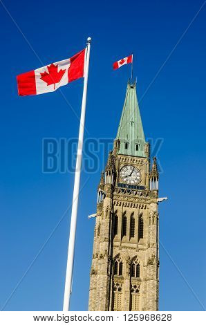 Close up of peace tower (parliament buiding) in Ottawa Canada with canadian flags.