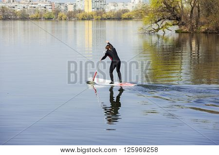 athletic man in a diving suit stand up paddle board on a background of the city