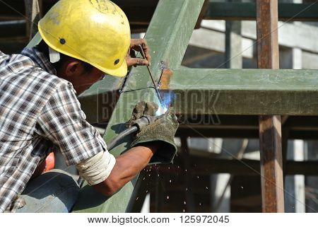 SELANGOR, MALAYSIA -DECEMBER 09, 2015: Welder wearing protective mask welding metal at the construction site.