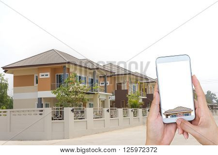 woman's hand hold and touch screen smart phone looking for a new houses in suburb.