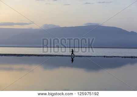 Man wearing black sports clothes walking on headland at the Dead Sea in early blue morning with mountains background