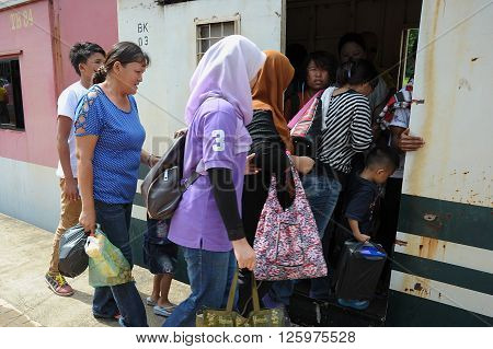 Tenom Sabah Malaysia - May 10 2014: Villager boarding train belong to Keretapi Negeri Sabah at Halogilat station. The train service is a main transportation in this rural area.