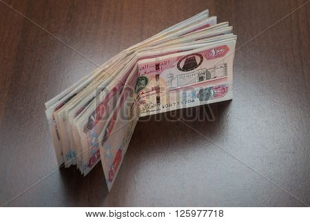 Currency notes of United Arab Emirates. Hundred Dirham notes stacked loosely together on dark background.