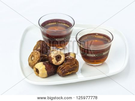 Arabic tea with dates. A typical food and drink traditionally offer to a guest in Arabic culture.