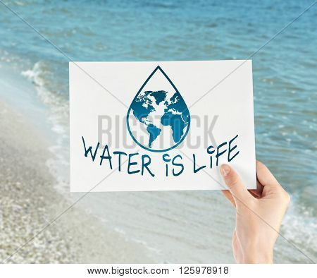 Save Water text on piece of paper in hand on sea water background