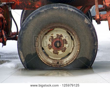 Tire on rusty equipment stuck in icy puddle