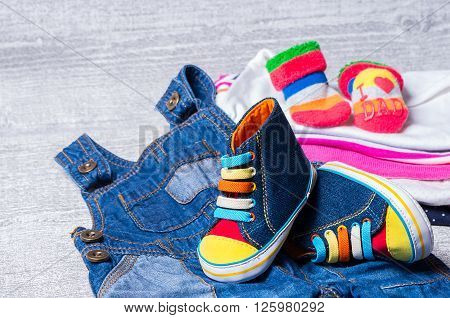 baby shoes for babies and a set of clothes in the background