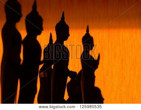 Silhouette of Buddha pouring water to Buddha statue in Songkran festival tradition of Thailand