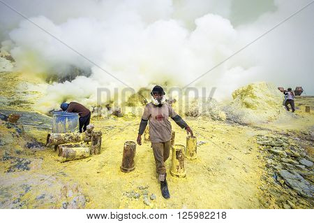 Kawah Ijen Volcano, East Java, Indonesia - May 25, 2013: Sulfur miners at work inside the crater of Kawah Ijen volcano in East Java, Indonesia.