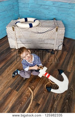 little boy sitting on the floor and holding the anchor looking at camera