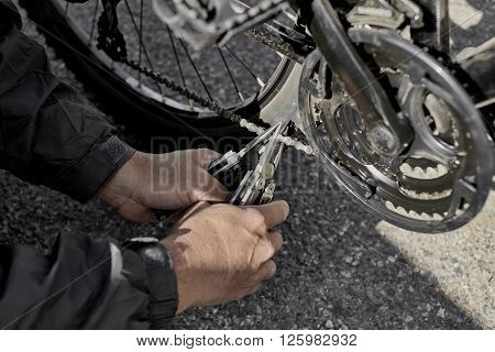 Man holding two pliers trying to fix bent bike chain