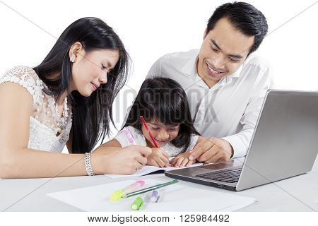 Picture of two young Asian parents teach their daughter to write on the book with a laptop on the table