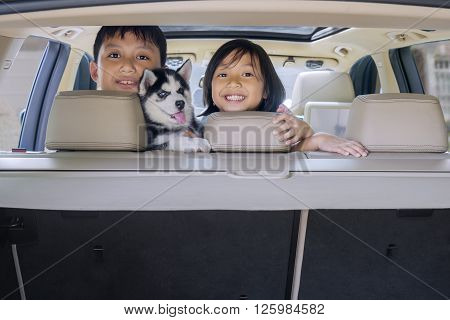 Portrait of two playful children with husky dog inside a car and smiling at the camera