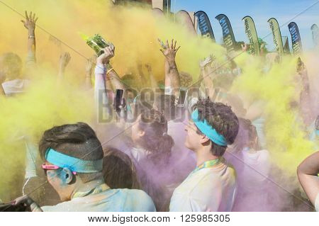 HAMPTON, GA - APRIL 2016: Runners who completed the Color Run toss packets of colored corn starch into the air creating an organic explosion of colors over the group in Hampton GA on April 2 2016 .