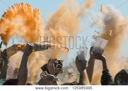 HAMPTON, GA - APRIL 2016: People's hands toss packets of colored corn starch in the air to create a color explosion at the Color Run  in Hampton GA on April 2 2016.