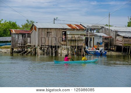Muisne, Ecuador - March 16, 2016: Slums in poor section of the city, in the coast of Ecuador, with houses on poles over the water