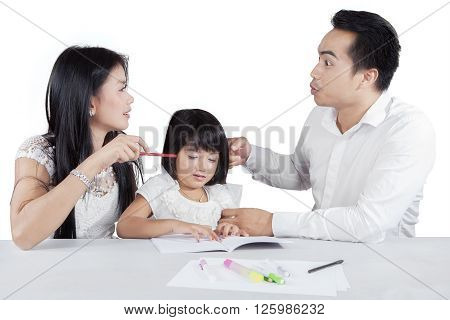 Picture of a sad girl studying with book while her parents quarreling isolated on white background