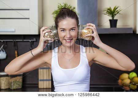 Young happy brunette woman holding cans of cereals in the kitchen