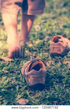 Child take off leather shoes. Close up child's foot learns to walk on grass reflexology massage. Kid relax in garden. Shallow depth of field (dof) selective focus. Retro style.