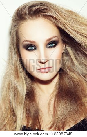 Vintage style portrait of young beautiful blond woman with long hair and smoky eyes