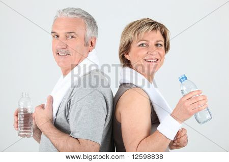 Senior man and senior woman drinking water after sports